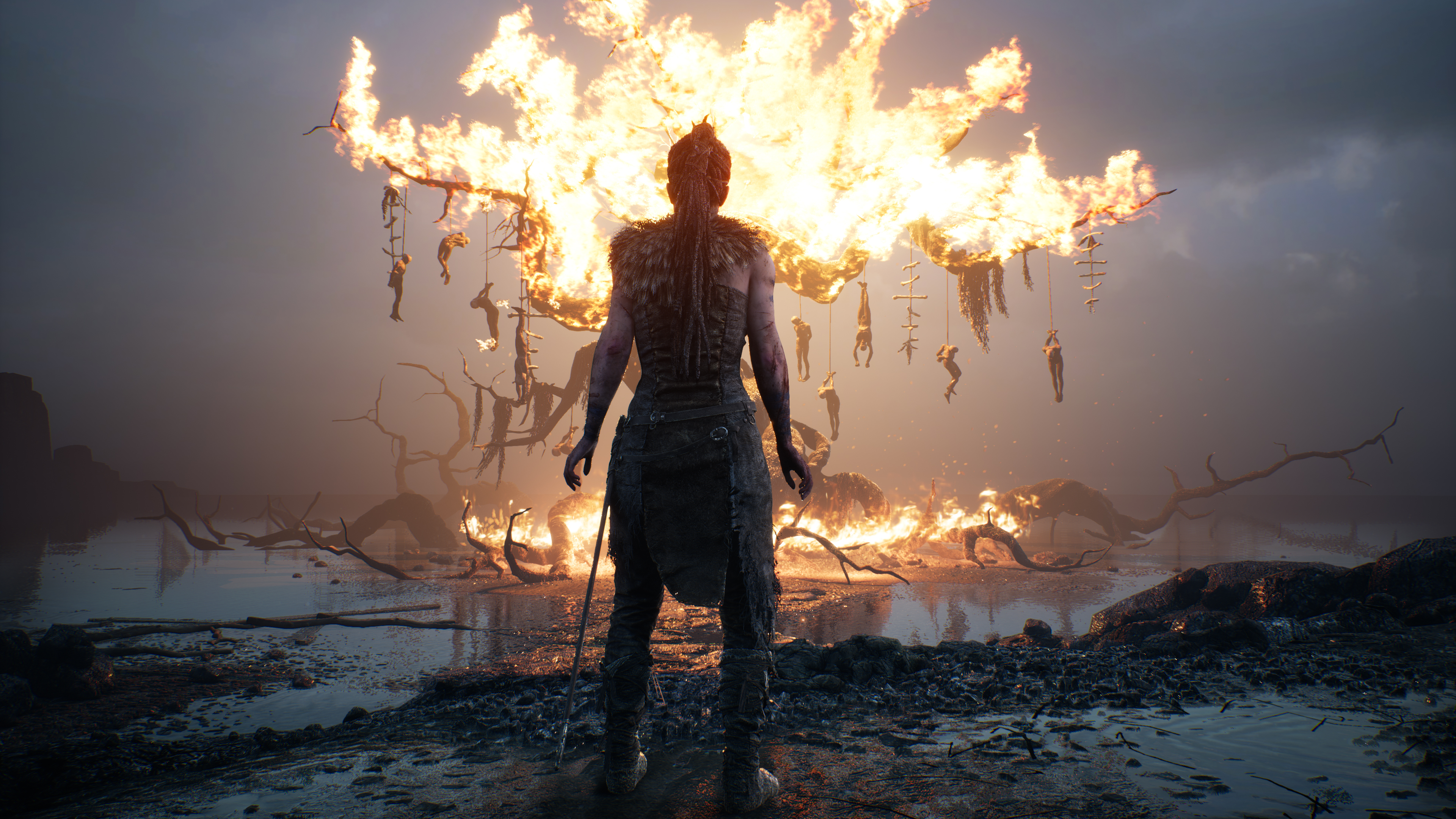 Senua in front of a burning tree with hanged people