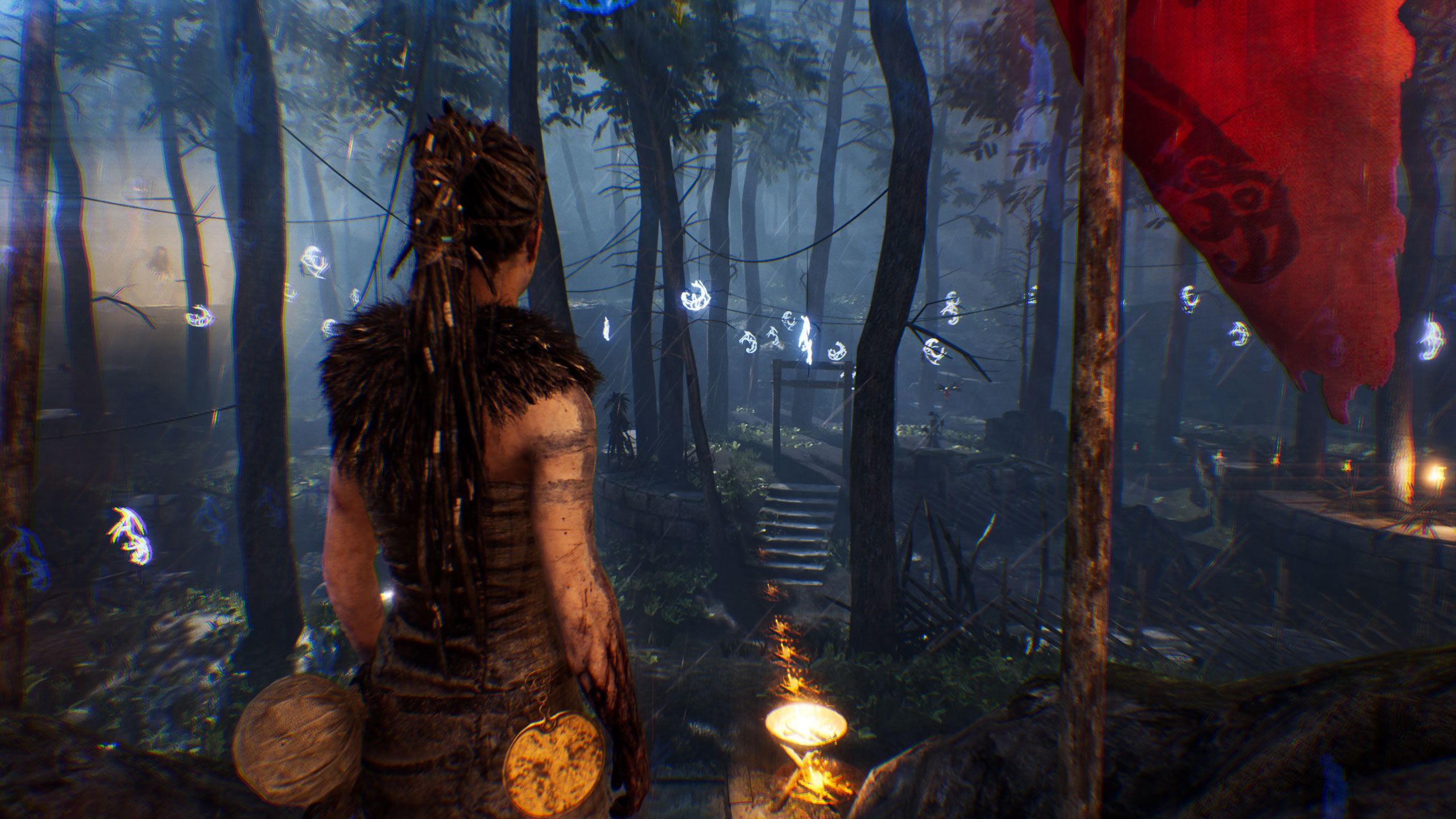 Senua in the woods with many hanging, glowing symbols