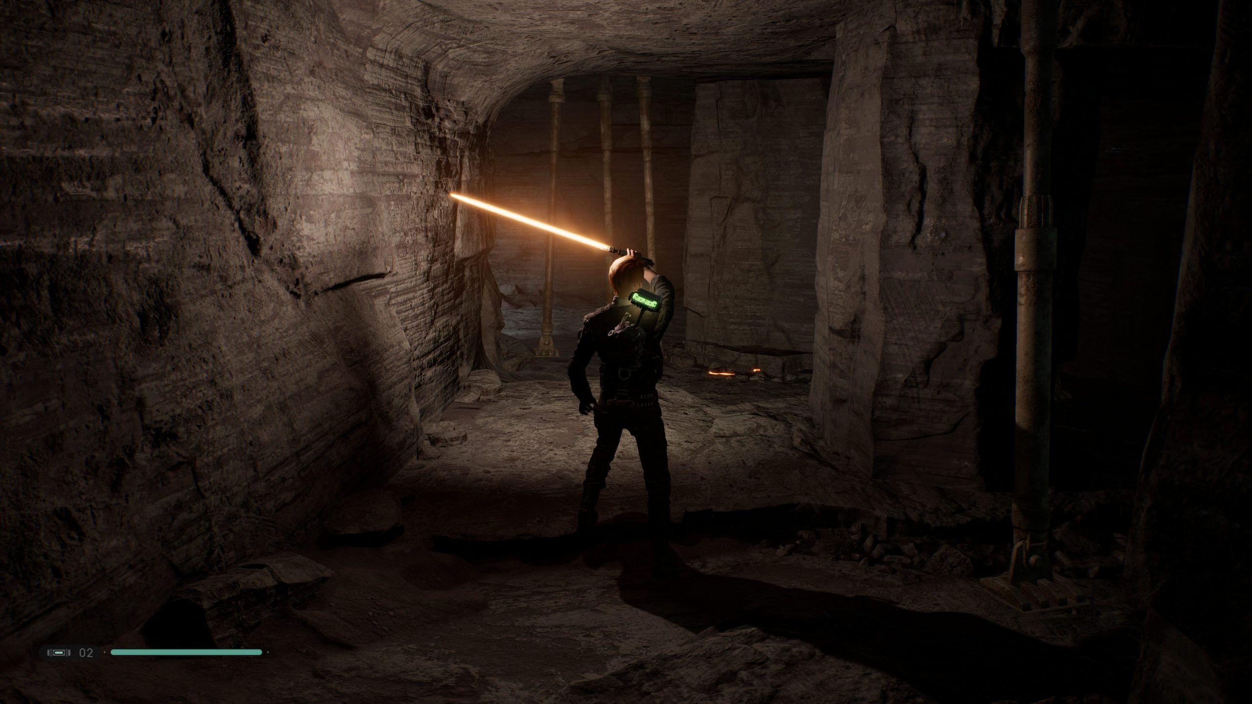 Cal using his lightsaber to light up a dark passage